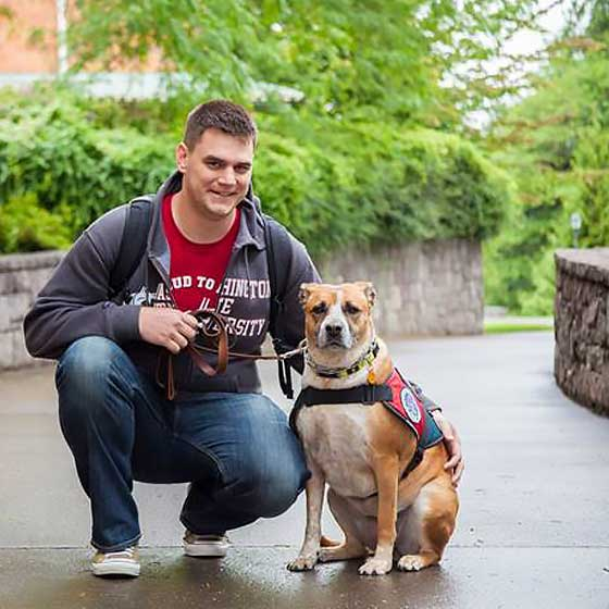 Male student on one knee next to service dog.